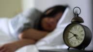 meisje slapen op bed, klok op het nachtkastje