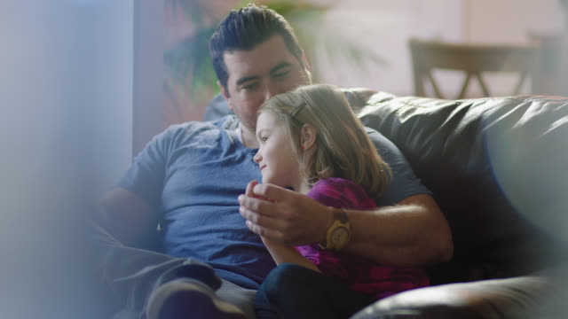 MS. Girl snuggles up with dad on comfortable couch as he holds her hand and kisses her forehead in sweet young family moment.
