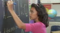 CU, Girl (10-11) solving math equation on blackboard, Richmond, Virginia, USA