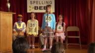 Girl spelling word at microphone in spelling bee / Los Angeles, California
