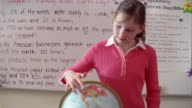 Girl spinning globe in front of classroom / stopping and pointing at Africa on globe / zoom in to girl pointing at Maine on globe / tilt up to girl smiling at camera / Gorham, Maine