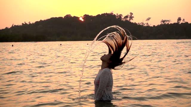 Girl Splashing Water with her Hair in the ocean