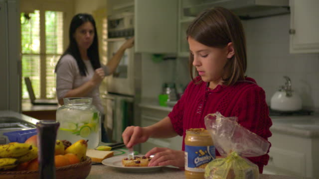 MS SELECTIVE FOCUS Girl (10-11) spreading peanut butter on bread in kitchen,  mother in background,, North Hollywood, California, USA