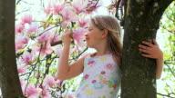 SLO MO MS Girl (8-9) standing at tree, smelling magnolia flower, Vrhnika, Slovenia