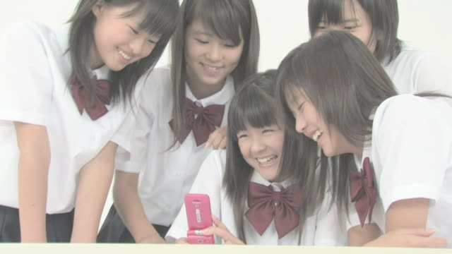 Girl students playing with cellular phone
