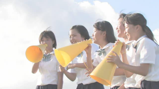 Girl students shouting with megaphones