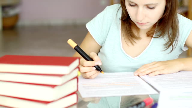 Girl studying and smiling into the camera