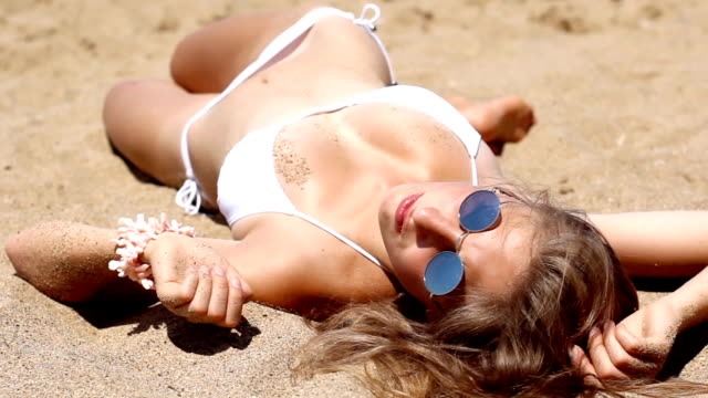 girl sunbathe on the sandy beach