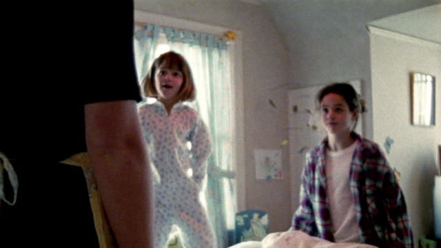 Girl + teen girl have pillow fight until they notice mother watching (arm in FG) / they look guilty