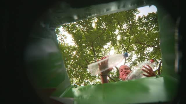 POV LA MS Girl (8-9) throwing plastic bottles into garbage bin, Panama City, Panama