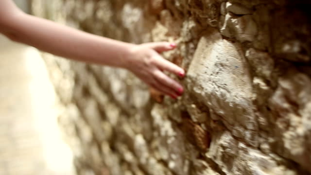 Girl touching old stone wall