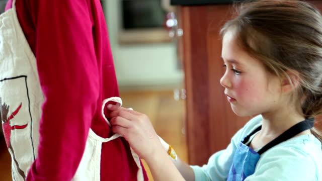 CU TU TD Girl (6-7) tying brother's (8-9) apron, Yarmouth, Maine, USA