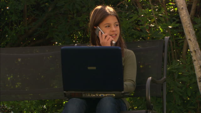 ZI, MS, Girl (10-11) using laptop and talking on mobile phone in garden, Los Angeles, California, USA