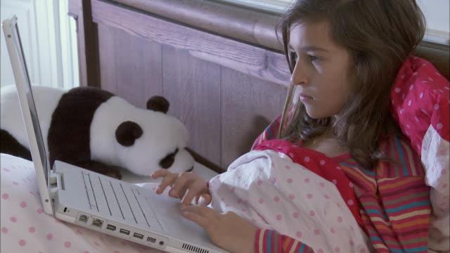 CU Girl (10-11) using laptop in bed / Brussels, Belgium