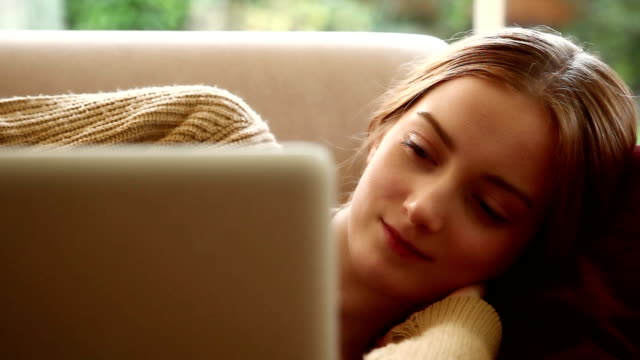 Girl using laptop, lying on a sofa.