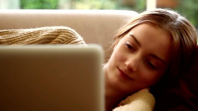 Girl using laptop, lying on a sofa.