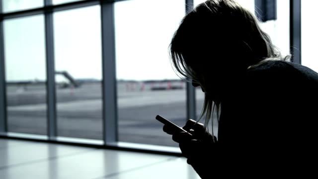 Girl using smart phone at airport terminal, waiting for flight
