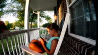 girl using smart phone on front porch of home