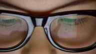 Girl using tablet reflected in glasses close up