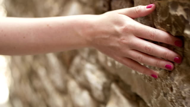 Girl walking and touching old wall