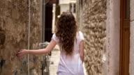 Girl walking between two old walls
