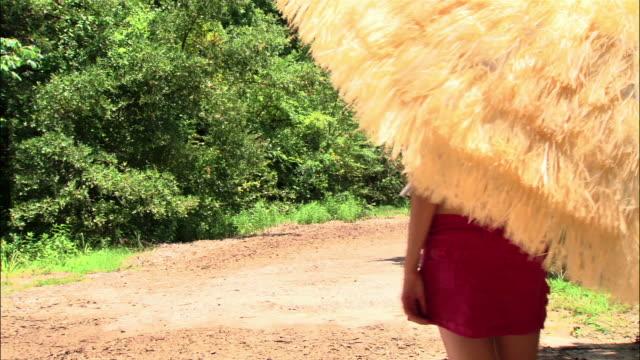 WS girl walking down dirt road under sunshade/ girl turning to look at camera/ girl walking away/ Texas
