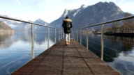 Girl walking on the lake dock and enjoying the view