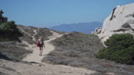 girl walks on the path of Capo Testa, Sardinia, Capo Testa, Olbia-Tempio. Santa Teresa di Gallura, peninsula eroded by winds