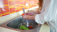Girl washes vegetables