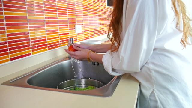 Girl washes vegetables