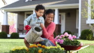 DS WS Girl waters flowers in garden with mother in front of house/ Richmond, Virginia USA