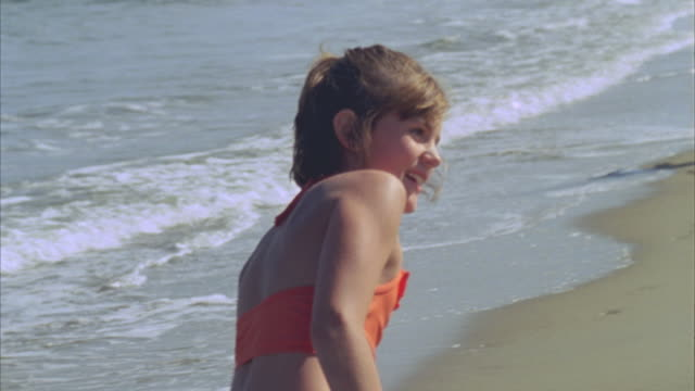 CU PAN WS Girl waving to camera near family playing on beach / Phippsburg, Maine, USA