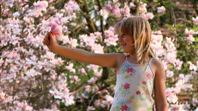 MS Girl (8-9) waving with magnolia flower, Vrhnika, Slovenia
