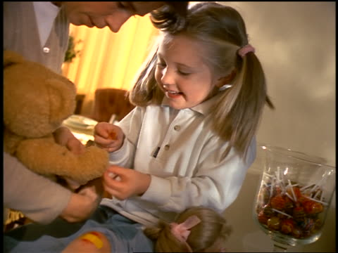 Girl wearing adhesive bandage on knee putting adhesive bandage on hand of teddy bear held by mother