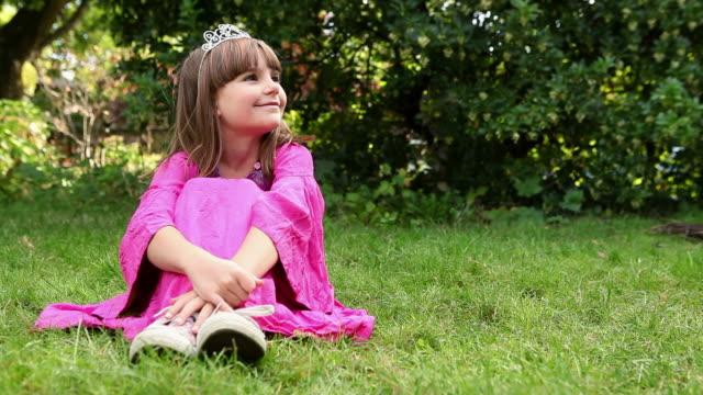 Girl wearing pink dress and tiara sitting on grass
