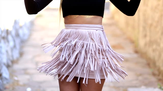 Girl wiggles her skirt with fringes
