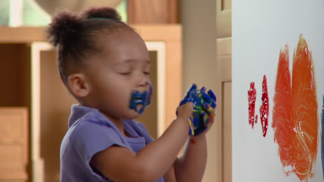CU Girl wiping paint on her mouth and then kissing wall near finger painting / Richmond, Virginia, USA