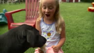 MS Girl (8-9) with black Labrador in playground, dog eating ice cream / Stowe, Vermont, USA