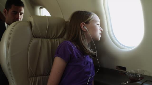 MS Girl (10-11) with earphones looking through window in airplane / Spanish Fork, Utah, USA