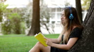 Girl with headphones reading a book in the park