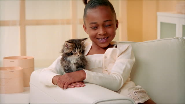 CU, Girl (6-7) with Maine Coon kitten sitting on sofa, portrait