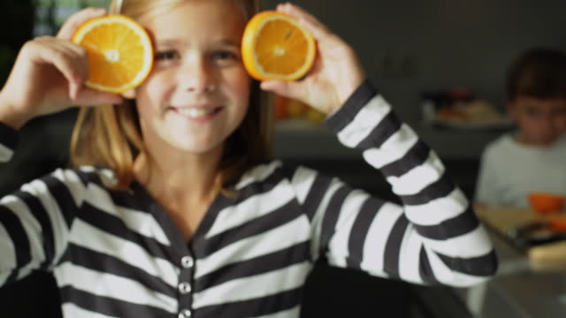 CU ZI Girl (10-11) with orange slices in front of eyes, boy (4-5) in background / Kleinmachnow, Brandenburg, Germany