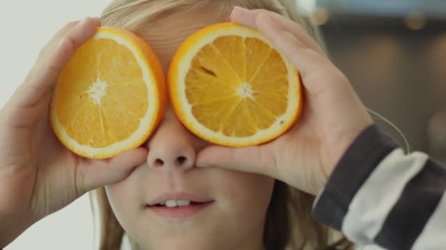 CU Girl (10-11) with orange slices in front of eyes / Kleinmachnow, Brandenburg, Germany