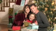 Girl with parents laughing by Christmas tree