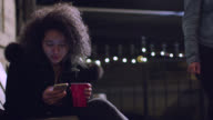 MS SLO MO. Girl with plastic drink cup texts on smartphone at party.
