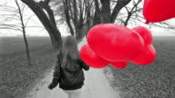Girl with red heart shaped balloons running in a park