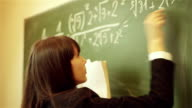 girl writing mathematical equation on chalkboard