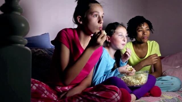 Girlfriends at sleepover eating popcorn watching TV