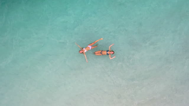 Girlfriends play in the turquoise waters and white silica sand beaches of Lake McKenzie.
