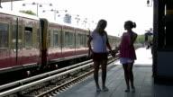 Girlfriends walking on train platform